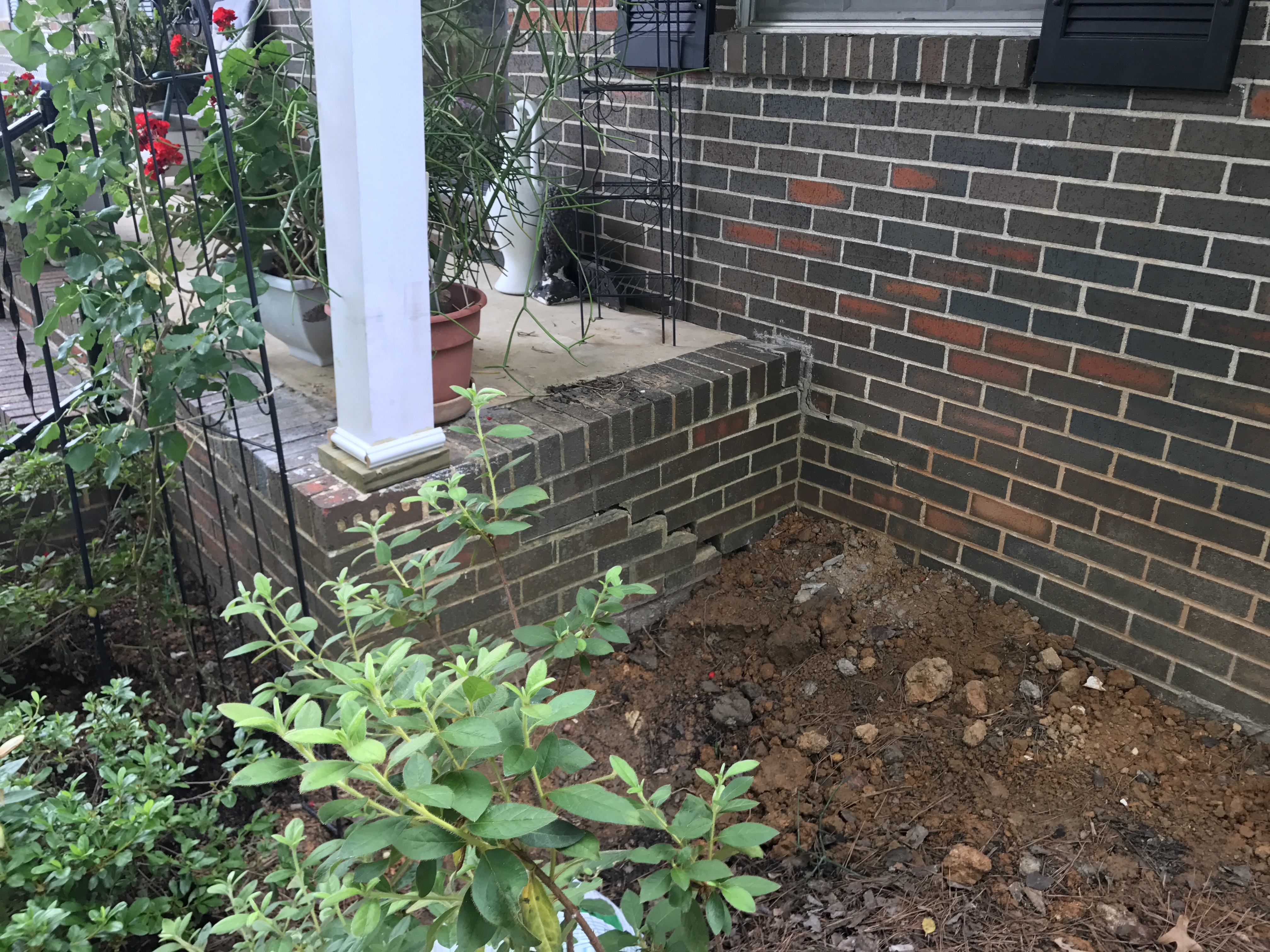 Stair stepping crack separating the mortar of the brick porch in Adamsville home